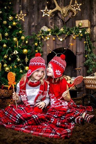 Opgroeiende kinderen, knus en fluisterend bij de kerstboom